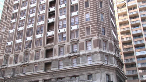 The camera zooms in on an older highrise building to a... Stock Video Footage