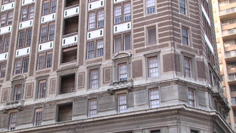 The camera zooms in on an older highrise building to a window with ornate masonry above and below it Footage