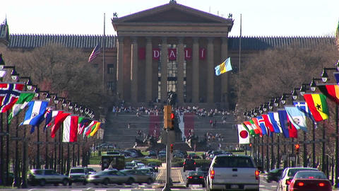 The camera pans up from the traffic and flags on Benjamin Franklin Parkway to the Philadelphia Museu Footage