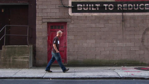 A young man walks by old building with a red door Stock Video Footage