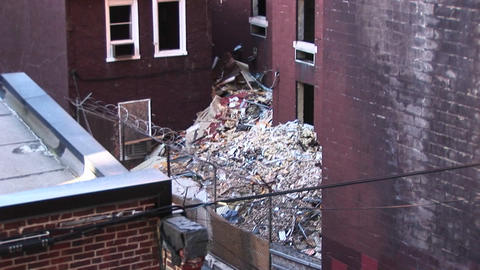 In this inner-scene the camera pans up and over a roof-top to view trash piling up around an old apa Footage