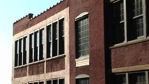 The camera zooms in on old red brick inner-city school building with dingy windows Footage