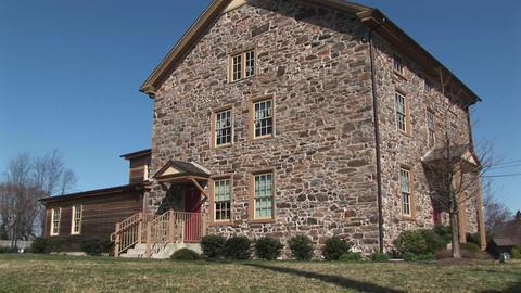 The camera zooms in on three-story fieldstone house to... Stock Video Footage