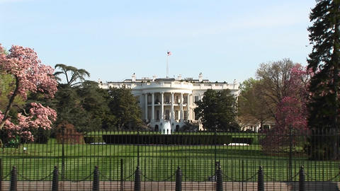 The camera zooms in for a closer look at the White House and the American Flag flying from the top o Footage