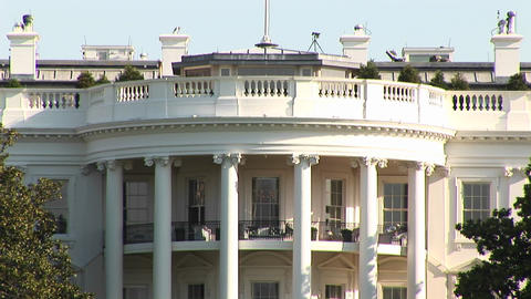 The camera pans-up the White House to the large flag-pole of the roof Footage