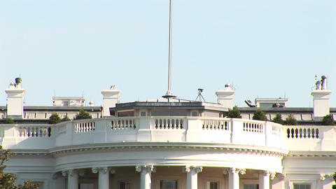 The camera pans-up the White House to the large flag-pole... Stock Video Footage