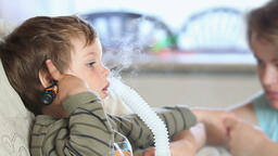 Mother and little boy using nebulizer to inhale medicine panning Footage