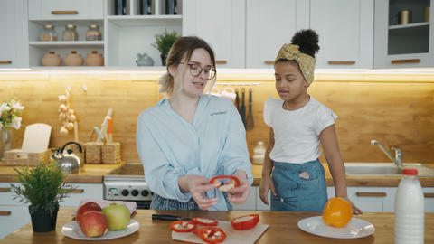 Happy cheerful mom teaches her daughter how to cook, joyful African girl laughs Live Action