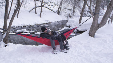 View of couple sitting in hammock tied up outside in the snow Live Action