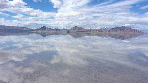 Aerial view flying low over water covering the Bonneville Salt Flats Live Action