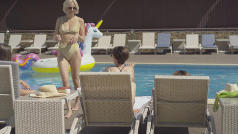 Cheerful woman in golden swimming suit and sunglasses putting on sun hat and Live Action