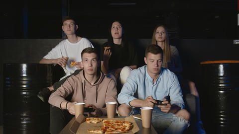 Students having fun with video game at home, young men winning doing high-five GIF