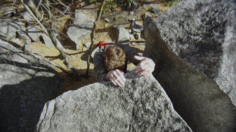 Top down view of as man climbs up boulder reaching the top Live Action