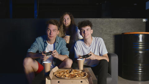 Happy company of the friends enjoy relaxing by playing videogames and having fun GIF