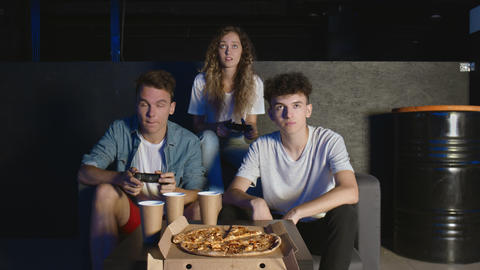 Group of friends having fun playing on game console in dark room. One man eats GIF
