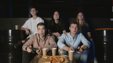 Group of upset friends relaxing on living room sofa and playing video games GIF