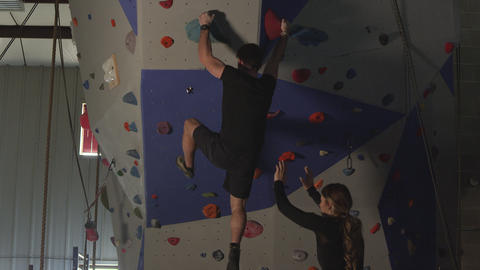 Couple in gym working out on rock climbing wall while he climbs Live Action