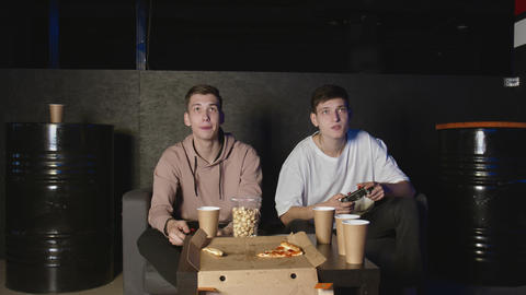 Two male friends winning in video game, sitting on couch, teenage friendship Live Action