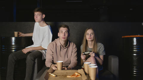 Happy group of friends playing video games and eating pizza at home GIF