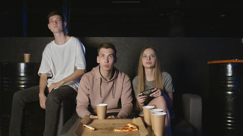 Upset group of friends losing video games and eating pizza at home GIF
