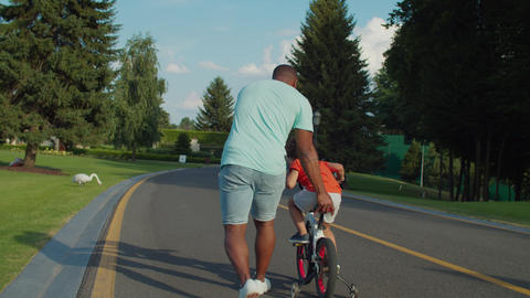 Rear view of caring dad helping son to ride bike Live Action