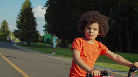 Portrait of joyful preschool child cycling outdoors Live Action