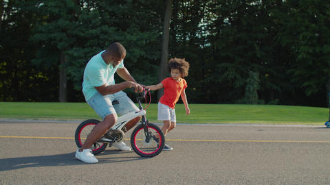 Mischievous father riding kids bicycle in park Live Action