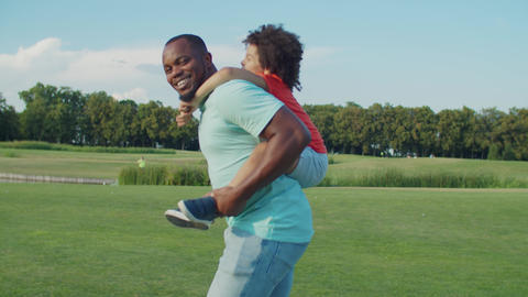 Joyful dad piggybacking excited son in nature Live Action