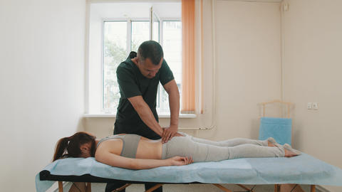 Osteopath treatment - the doctor pushing on the butt of young woman Live Action