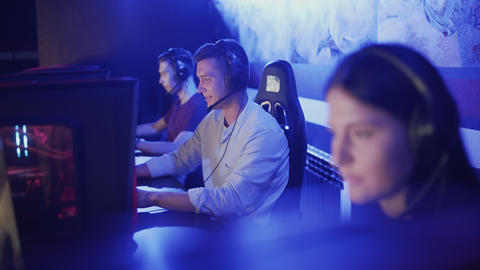 Professional cyber sport gamers playing in online video game. Young upset team Live Action