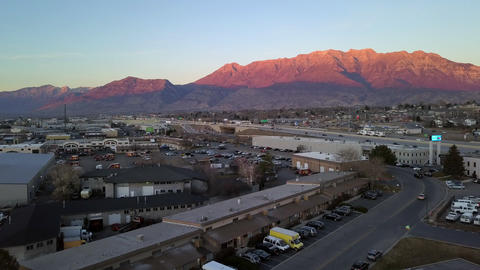 Aerial view rising above building to view mountain lit up by the sun Live Action