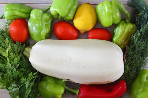 Red pepper, zucchini, green pepper, parsley, dill, tomato, lemon on a brown wooden background top フォト