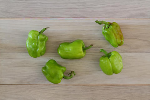 Organic green pepper in wooden plate on dark wooden table background, top view, copy space フォト