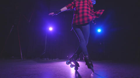 Close-up panoramic view of sporty pretty young girl spinning on roller skates in Live Action