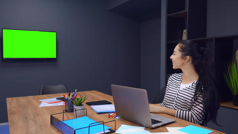 Cheerful laughing of working woman who is looking at TV with green screen Live Action