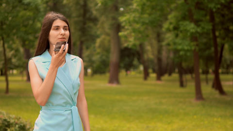 businesswoman dictates voice message walks along alley with trees Live Action