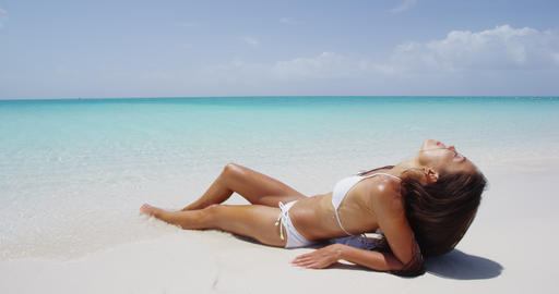 Skin care and body care - woman sun tanning with perfect skin on beach Live Action