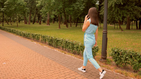 trendy girl in comfortable shoes stroll in park Live Action