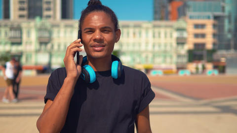 cheerful young man talk by phone walking on the street Live Action