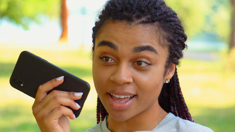 close up girl dictates voice message use mobile in park Live Action