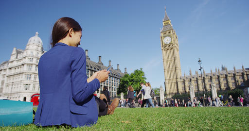 London business woman using phone relaxing on Parliament Square in London Live Action