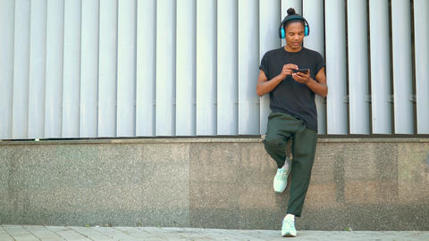 handsome young man with headphones using mobile phone outdoor Live Action