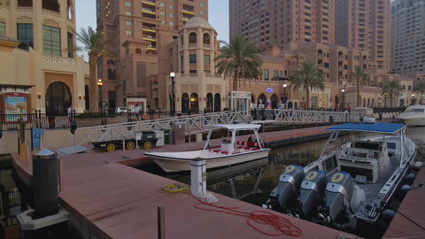Porto Arabia Marina in The pearl Doha, Qatar daylight summer shot showing luxurious yachts and boats Live Action