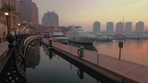 Porto Arabia Marina in The pearl Doha, Qatar sunset summer shot showing luxurious yachts and boats Live Action