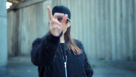 Woman showing v sign on urban street. Serious lady showing peace sign outdoors Live Action