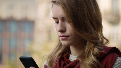Focused woman waiting email on phone outdoors. Closeup girl touching cellphone Live Action