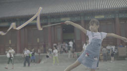 Girl playing with ribbon on the street . Beijing. China Live Action