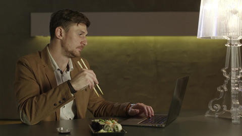 Hungry European businessman eating sushi with chopsticks Footage