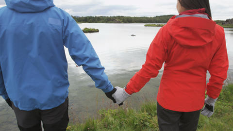 Couple holding hands enjoying view of nature lake Live Action