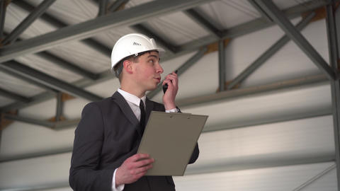 A young man in a helmet with documents speaks on a walkie-talkie at a ライブ動画